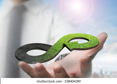 Green circular economy concept. Man's hand showing arrow infinity symbol with grass texture.