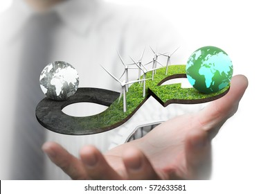 Green circular economy concept. Man's hand showing arrow infinity symbol of grass texture with wind turbines and two globes of different colors.
