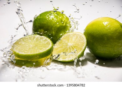 """Green citrus fruit lime """"Citrus aurantiifolia"""", the fruit of the tree on the kitchen table in the water.  White, gray background. Splash of water with drops, slow motion, close-up photo."""