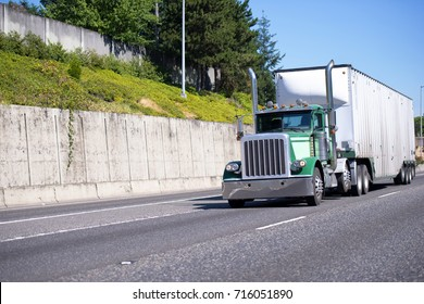 Green classic big rig semi truck with tall exhaust chrome pipes and heavy duty roomy bulk semi trailer transporting industrial processing cargo on divided highway with cascade concrete wall