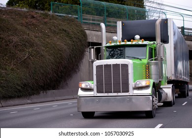 Green classic pro American idol big rig semi truck fleet with tall chrome pipes transporting goods in covered semi trailer on wide highway with protected bridge and bushes