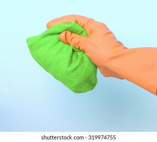 Green cleaning rag in gloved hand