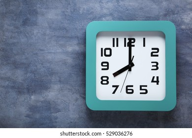 Green clock on a grey wooden table