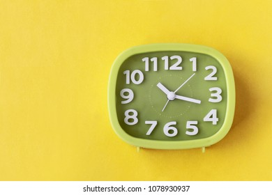 Green clock with white numbers and arrows on yellow background