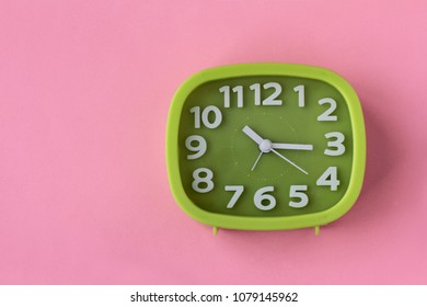 Green clock with white numbers and arrows on pink background