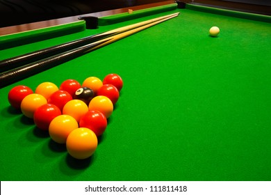 A green cloth billiards or pool table with english league red and yellow balls