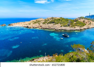 Green coast and view of boats on sea in Cala Portinatx bay, Ibiza island, Spain