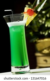 Green cocktail with alcohol over black background