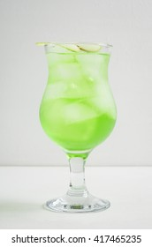 Green cocktail with apple slice on the white background