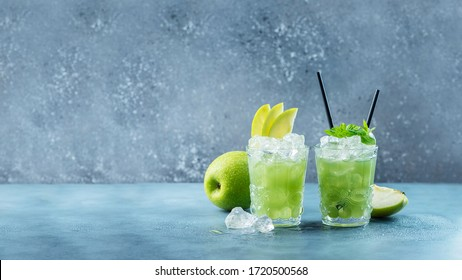 Green cocktail with ice and mint. Bar concept. Apple mojito with mint and ice on the blue background, selective focus image and slider format