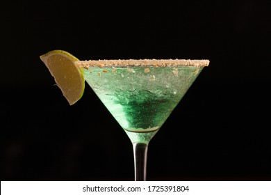 green cocktail in a martini glass rim covered with salt. with a slice of lime. close-up on a black background. macro