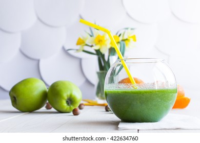 green cocktail in a transparent glass on a white wooden background