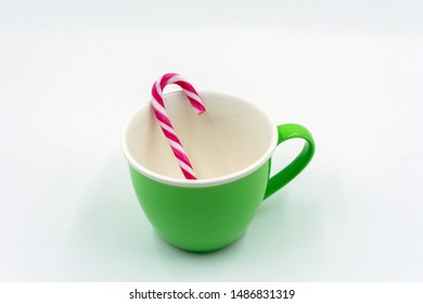 green coffee cup with candy cane. On a neutral background