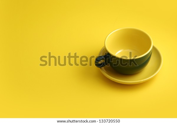 green coffee cup on yellow background