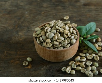 green coffee grains on wooden background