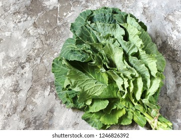 Green Collard bunch of leaves on concrete background. organic nutrition concept. raw foods kale. Raw Green Organic Collard Greens