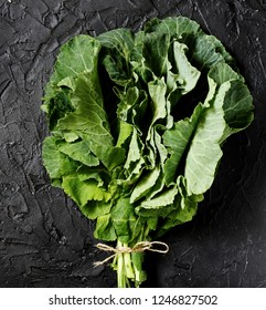 Green Collard bunch of leaves on black background. organic nutrition concept. raw foods kale. Raw Green Organic Collard Greens