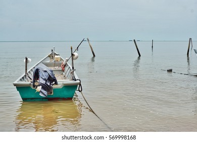 green color fisherman small boat mooring at the seaside of Port Dickson beach of Malaysia