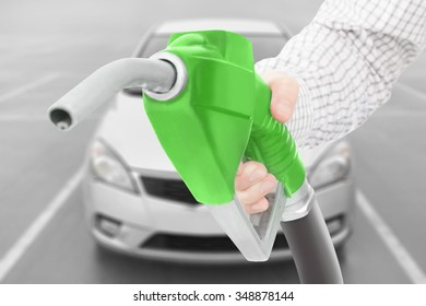 Green color fuel pump gun in hand with car on background