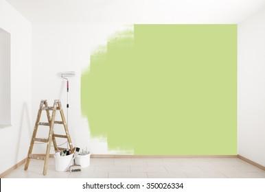 mit grüner Farbe an einer Wand mit Leiter und Malwerkzeugen lackiert