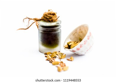 Green colored dry fruit essence of Green cardamom or elaichi isolated on white in transparent bottle.