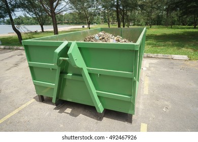 Green colored dump bin at open space parking area.