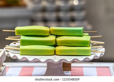 Green colored popsicles on a white platter.