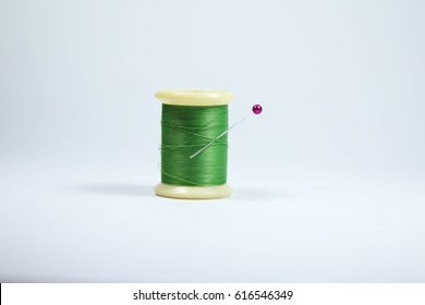 Green colored sewing thread on white background. Green sewing thread on white background with needle. Spool of thread with needle on white background with copy space.