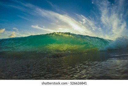 Green colored small wave with the sun setting
