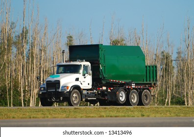 Green colored waste removal dump truck