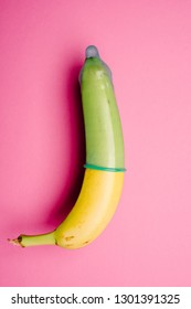 Green condom on fresh banana in front of pink background
