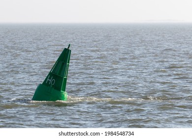 Green conical buoy floats in the North Sea off Hallig Hooge