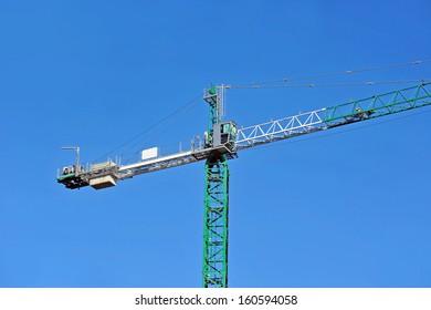 Green construction tower crane against blue sky