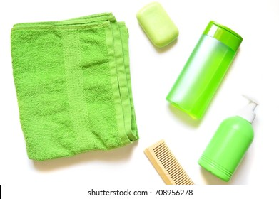 Green cosmetic bottles, terry towel, soap bar and hair brush. Shampoo or balm, liquid soap on a white background. Flat lay toiletries, organic cosmetics, bath products, shower stuff. Top view photo