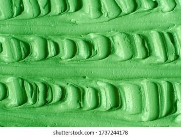 Green cosmetic clay (cucumber facial mask, avocado face cream, green tea matcha body wrap) texture close up, selective focus. Abstract background with brush strokes.
