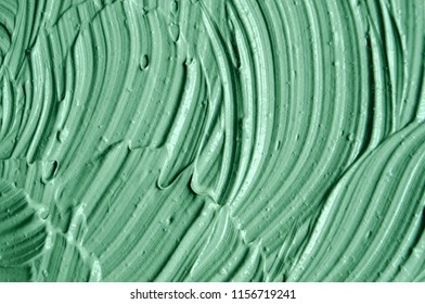 Green cosmetic clay (facial mask, cream, body scrub) texture close up, selective focus. Abstract background with brush strokes.
