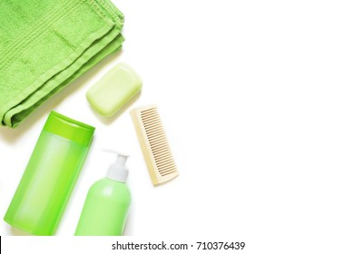 Green cosmetics bottles. Liquid soap, shampoo, terry towel and wooden hair brush on white background. Flat lay bath products, top view. Cosmetics for bathroom and shower. Free space for text, mock up