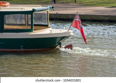 green and cream river boat makes its way along river with union jack ensign