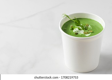 Green cream soup in paper package or disposable cup with pea and spirulina. Vegan food delivery concept. mock up