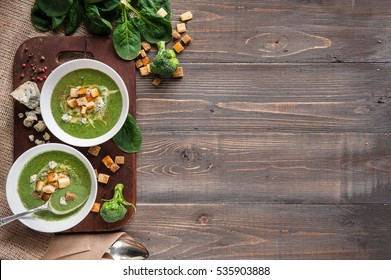 Green cream soup of spinach and broccoli. with the addition of parmesan and blue cheese with croutons. a wooden background.  conception healthy food and diet.