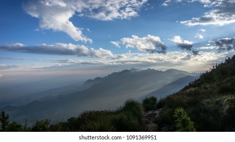 Green and creepy nature of the Serra da Mantiqueira at sunset with solar rays visible in the mist of Brazilian winter and beautiful blue sky filling the image.