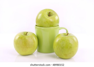 green cup and apples