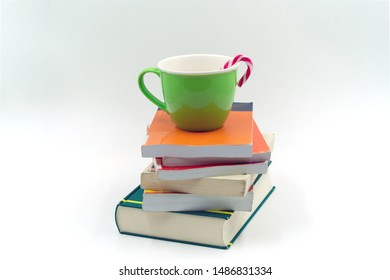 green cup with candy cane on a stack of books. On white background