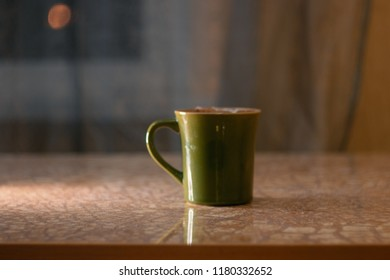 Green cup of coffee and blurred Moon in window, copyspace