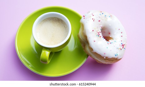 green cup of coffee with donut on pink plate