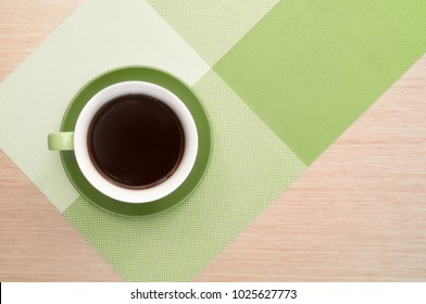 Green cup of coffee on the table background and tablecloth. Coffee time