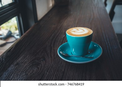the green cup of coffee on wood table in vintage color mood