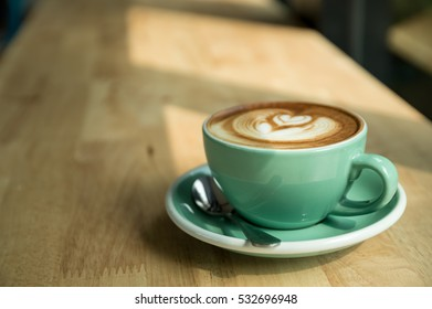 Green cup of latte art coffee on wooden table