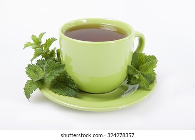 Green cup of  tea with lemon balm herb on a white background.