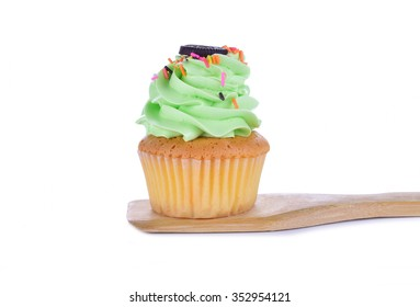 Green cupcakes on a spatula on a white background.
